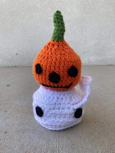 A crochet pumpkin head on top of a crochet mummy head