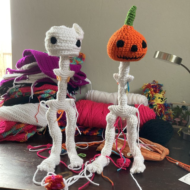 Two amigurumi skeletons in need of arms and wearing their crochet heads
